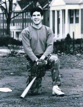 Peter G. in college kneeling on one knee with baseball bat and glove