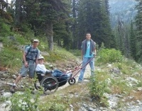 Family of three hiking with a trail buddy for wheelchair access