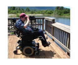 Man in wheelchair with fishing rod and scope on a deck overlooking a lake