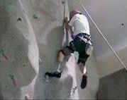 Person with prosthetic leg climbing indoor climbing wall
