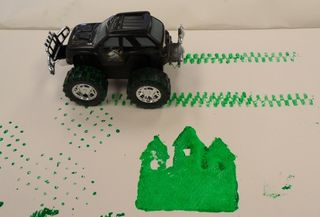 Toy car applying paint to paper