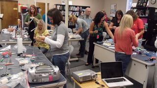 Photo of busy adapted music workshop attendees in the resource room
