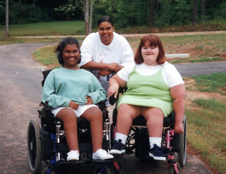 Photo of Liz as a child seated in her powerchair with another camper, also in a power chair, and a counselor leaning in between them.