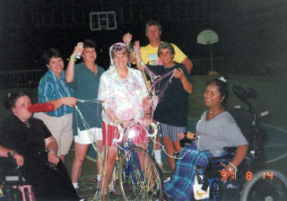 Photo of a group of camp staff and Liz smiling with silly string draped over one adult on a bicycle.